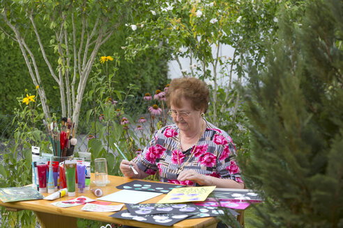 Germany, Bavaria, Ingolstadt, senior woman painting in garden - MABF000184