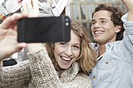 Portrait of happy young couple photographing themself with smart phone, studio shot - FMKF000930
