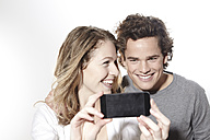 Portrait of happy young couple with smart phone, studio shot - FMKF000950