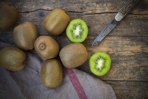 Kiwis (Actinidia deliciosa) and pocketknife on wooden table - LVF000381