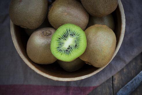 Bowl of kiwis (Actinidia deliciosa) on wooden table - LVF000379