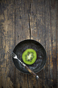 Bowl with half of a kiwi (Actinidia deliciosa) and a fork on wooden table - LVF000378