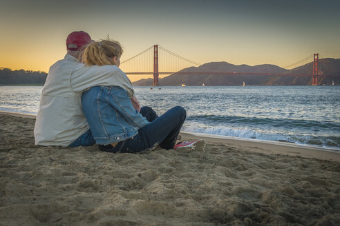 USA, California, San Francisco, Mature couple sitting at the beach at the Golden Gate Bridge at twilight - ABAF001086