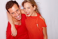 Portrait of happy young couple dressed in red - CHAF000118