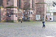 Germany, Baden-Wuerttemberg, Freiburg, Young man running behind pigeon - DRF000334