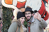 Portrait of smiling young couple photographing themself - DRF000333