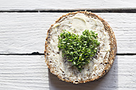 Slice of wholemeal bread with cress, heart-shaped on wooden table - SARF000157