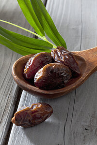 Wooden spoon with dates on wooden table - CSF020486