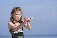 Germany, Mecklenburg-Western Pomerania, Rugia, Sellin, portrait of girl playing at seashore - PA000089