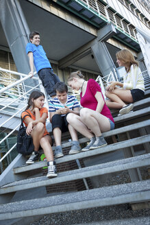 Teenage friends using mobile devices on stairs - MVC000049