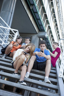 Teenage friends using mobile devices on stairs - MVC000051