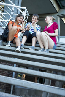 Teenage friends using mobile devices on stairs - MVC000048