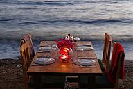 Turkey, Bodrum, Guemuesluek, Laid table on beach at dusk - SIEF004865