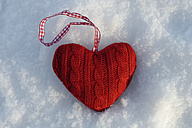 Red knitted heart lying on snow, close-up - LB000442
