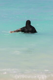 Maldives, Muslim woman in the ocean with traditional clothing - AM001448