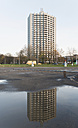 Germany, North Rhine-Westphalia, Aachen, Europaplatz, high-rise building reflecting at puddle - HLF000305