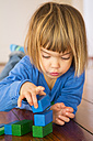 Little girl playing with blue and green wooden building bricks - LVF000393