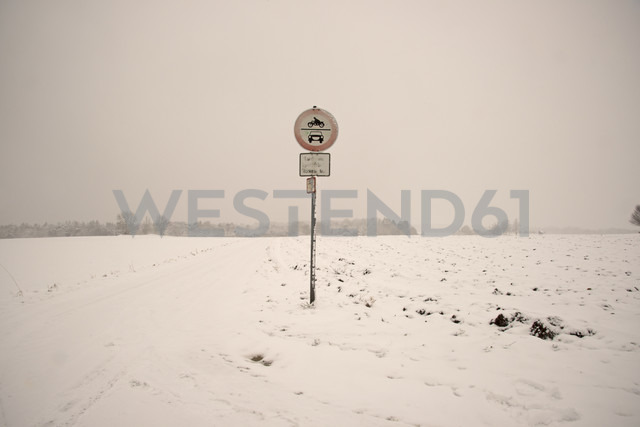 Snow covered landscape with traffic sign at field path - WGF000153
