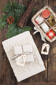 Christmas gift with gift tag and wrapping material on wooden table - ECF000420