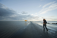 Great Britain, England, Northumberland, Holy Island, Lindisfarne, man walking on road at high tide - PA000139