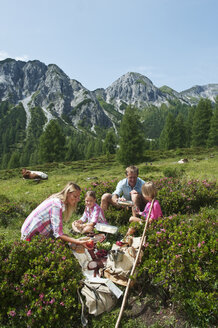 Austria, Salzburg State, Altenmarkt-Zauchensee, family with to children having a picnic on alpine meadow - HHF004723