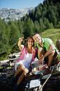 Austria, Salzburg State, Altenmarkt-Zauchensee, couple having a picnic on alpine meadow - HHF004717