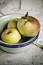 Bowl with three apples on wooden table - SBDF000369