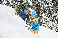 Austria, Salzburg Country, Altenmarkt-Zauchensee, Family walking in snow, carrying Christmas tree - HHF004665