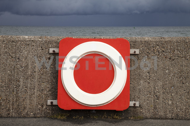 Germany, Fehmarn, Puttgarden, Life belt at harbour wall - WIF000237