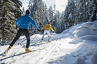 Austria, Salzburg Country, Altenmarkt-Zauchensee, Young couple cross-country skiing - HHF004655