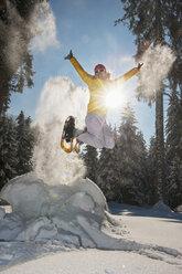 Austria, Salzburg State, Altenmarkt-Zauchensee, Woman with snowshoes jumping in winter landscape - HHF004692