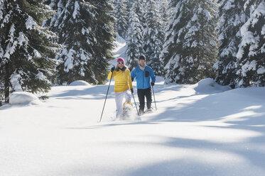 Austria, Salzburg State, Altenmarkt-Zauchensee, Couple snowshoeing in winter landscape - HHF004676