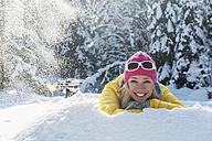 Austria, Salzburg State, Altenmarkt-Zauchensee, Smiling young woman lying in snow, portrait - HHF004674