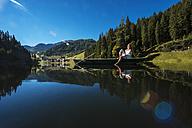Austria, Salzburg State, Altenmarkt-Zauchensee, woman sitting in a boat - HHF004696