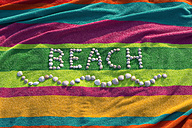 The word 'beach' formed by shells lying on a multicolored bath towel - ASF005264