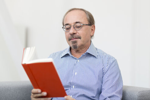 Germany, Senior man reading book - DR000347
