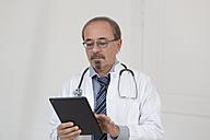 Germany, Doctor using digital tablet - DR000349