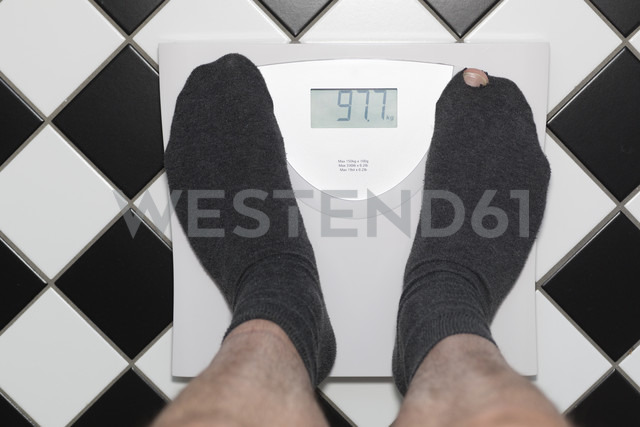 Germany, Senior man with hole in socks standing on bathroom sclaes - DR000340 - Stefan Rupp/Westend61