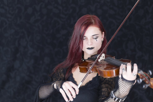 Young woman dressed in Gothic style playing violin with closed eyes - DR000352
