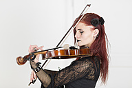 Young woman dressed in Gothic style playing violin with closed eyes - DRF000353