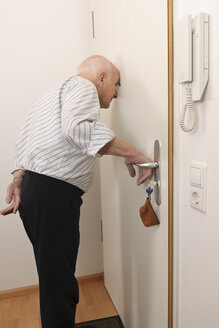Old man looking through peephole of apartment door - LAF000381
