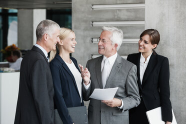 Smiling businesspeople talking in office - CHAF000015
