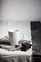 White mug, wire whip and pieces of chocolate on wooden table - SBDF000399