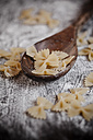 Farfalle on wooden spoon and wooden table with flour - SBDF000396
