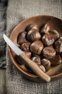 Chestnuts in wooden bowl, knife on top - SBDF000388