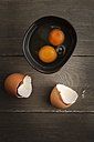 Bowl of two breaked open eggs and egg shells on wooden table, studio shot - EVGF000311