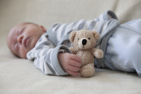 Portrait of sleeping baby boy lying on blanket with teddy - RBF001608