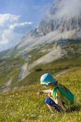 Italy, Province of Belluno, Veneto, Auronzo di Cadore, little boy crouching on alpine meadow near Tre Cime di Lavaredo - MJF000486