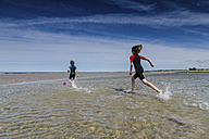 UK, Scotland, Burghead Bay, Children running in water - PAF000150