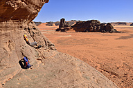 Algeria, Sahara, Tassili N'Ajjer National Park, Tadrart region, hiker leaning on rock face - ES000866